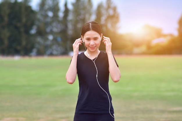 Hörende musik der schönheits-asiatinnen, wenn laufender morgen der übung am stadtpark