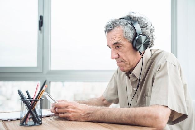 Hörende musik des älteren mannes auf kopfhörer am schreibtisch nahe dem fenster