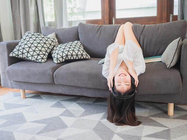 Hörende musik des asiatischen mädchens in den kopfhörern auf sofa