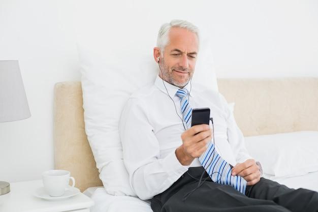 Hörende musik des geschäftsmannes mit seinem telefon im bett