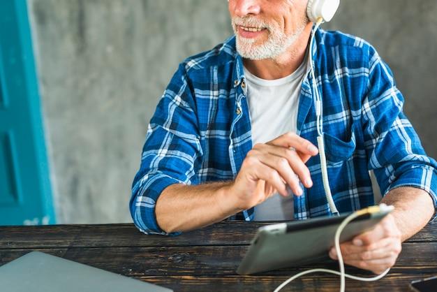 Hörende musik des glücklichen älteren mannes durch kopfhörer auf digitaler tablette