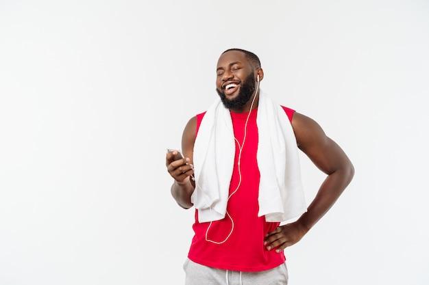 Hörende musik des hübschen afroamerikanermannes auf seinem tragbaren gerät nach sportübung.
