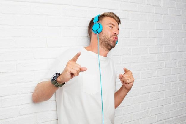 Hörende musik des hübschen blonden mannes mit kopfhörer