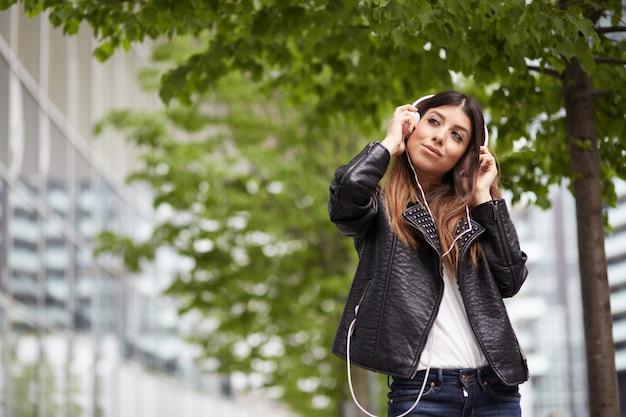 Hörende musik des hübschen brunette und unterhaltung mit mobile