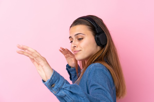 Hörende musik des jugendlichmädchens und tanzen über lokalisierte rosa wand