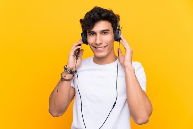 Hörende musik des jungen argentinischen mannes mit einem mobile über lokalisierter gelber wand
