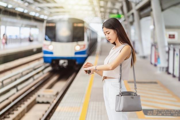 Hörende musik des jungen asiatinpassagiers über intelligenten handy und schauen des zugs mit handuhr in der u-bahnbahnstation, im japaner, im chinesen, im koreanischen lebensstil, im pendler und im transport