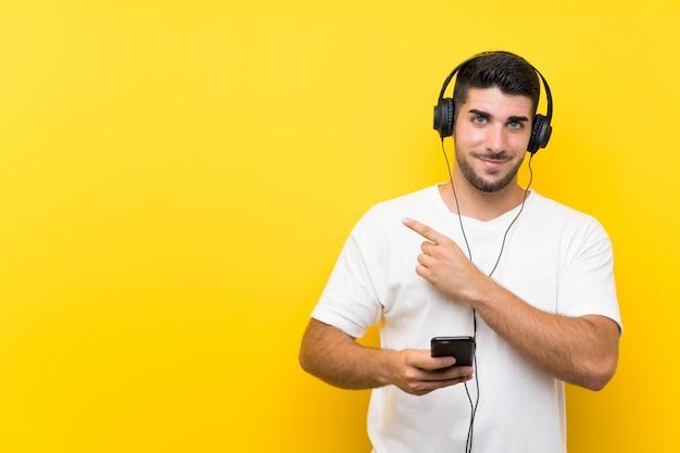 Hörende musik des jungen gutaussehenden mannes mit einem mobile auf gelber wand zeigend auf die seite, um ein produkt darzustellen