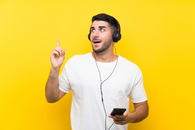 Hörende musik des jungen gutaussehenden mannes mit einem mobile über der lokalisierten gelben wand, die beabsichtigt, die lösung zu verwirklichen