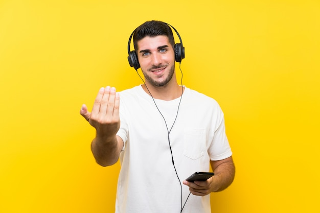 Hörende musik des jungen gutaussehenden mannes mit einem mobile über der lokalisierten gelben wand, die einlädt, mit der hand zu kommen. schön, dass sie gekommen sind