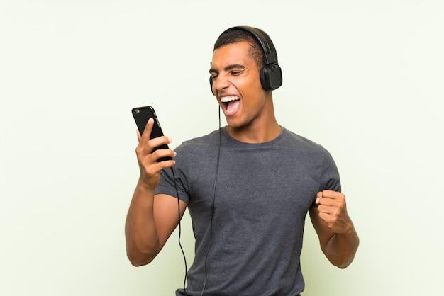 Hörende musik des jungen gutaussehenden mannes mit einem mobile über grüner wand