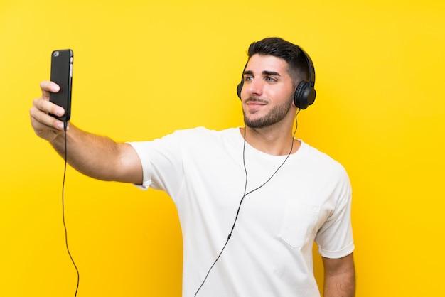 Hörende musik des jungen gutaussehenden mannes mit einem mobile über lokalisierter gelber wand