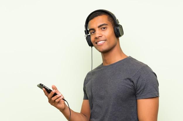 Hörende musik des jungen gutaussehenden mannes mit einem mobile über lokalisierter grüner wand