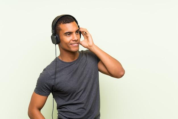 Hörende musik des jungen gutaussehenden mannes mit einem mobile
