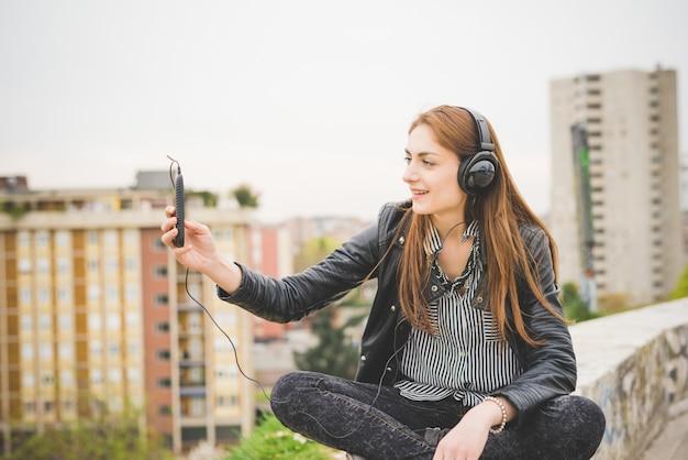 Hörende musik des jungen hübschen brunettemädchens