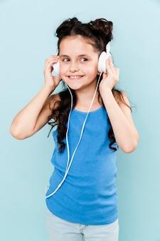 Hörende musik des jungen mädchens der vorderansicht