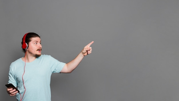 Hörende musik des jungen mannes auf kopfhörer durch handy ihren finger gegen graue wand zeigend