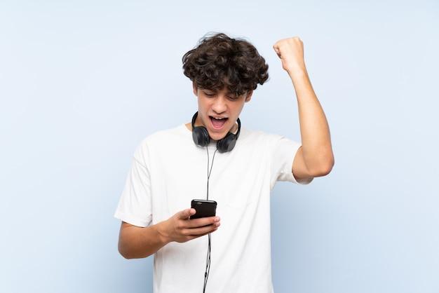Hörende musik des jungen mannes mit einem mobile über der lokalisierten blauen wand, die einen sieg feiert