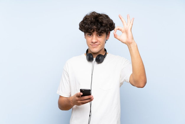 Hörende musik des jungen mannes mit einem mobile über der lokalisierten blauen wand, die okayzeichen mit den fingern zeigt
