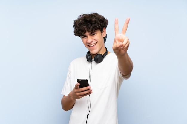 Hörende musik des jungen mannes mit einem mobile über lokalisierter blauer wand lächelnd und siegeszeichen zeigend