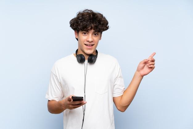 Hörende musik des jungen mannes mit einem mobile über lokalisierter blauer wand überraschte und finger auf die seite zeigend