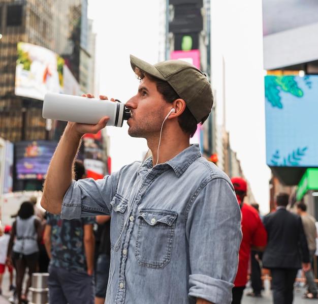 Hörende musik des jungen mannes und trinken von der thermosflasche