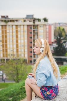 Hörende musik des jungen schönen blonden kaukasischen mädchens