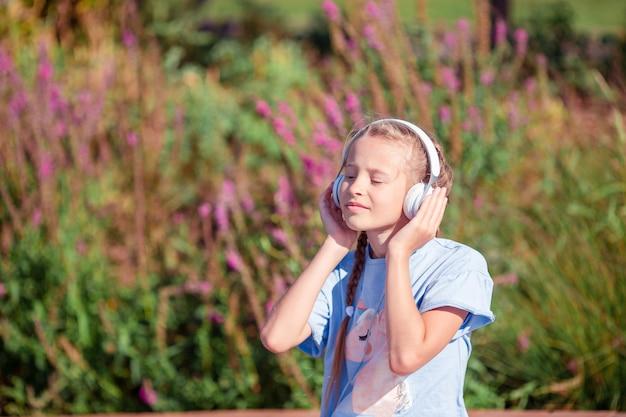 Hörende musik des kleinen entzückenden mädchens im park