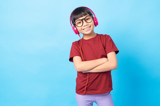 Hörende musik des thailändischen asien-mädchenkindes, tragender rosa kopfhörer