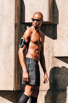 Hörende musik eines beschissenen jungen muskulösen mannes am handy im armbindenfall, der weg schaut