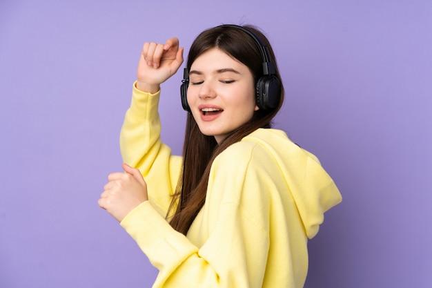 Hörende musik und tanzen der jungen ukrainischen jugendlichfrau
