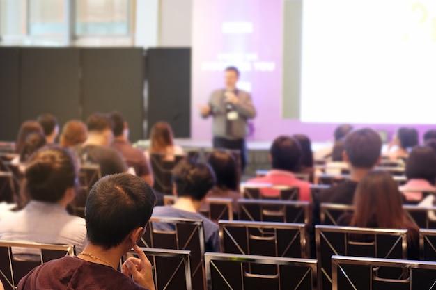 Hörender sprecher der publikum, wer vor dem raum im konferenzsaal steht