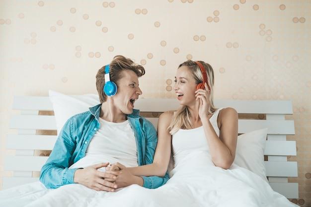 Hörendes lied des glücklichen paars morgens am schlafzimmer