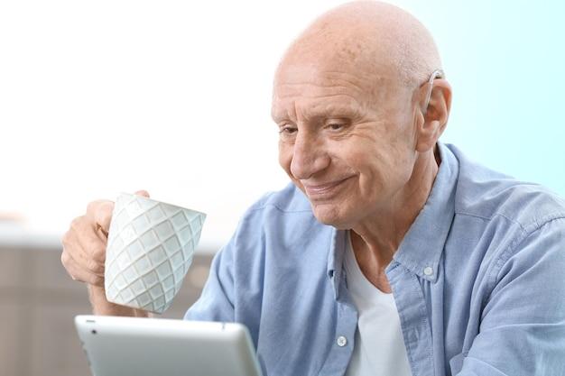 Hörgeschädigter mann mit tablette zu hause