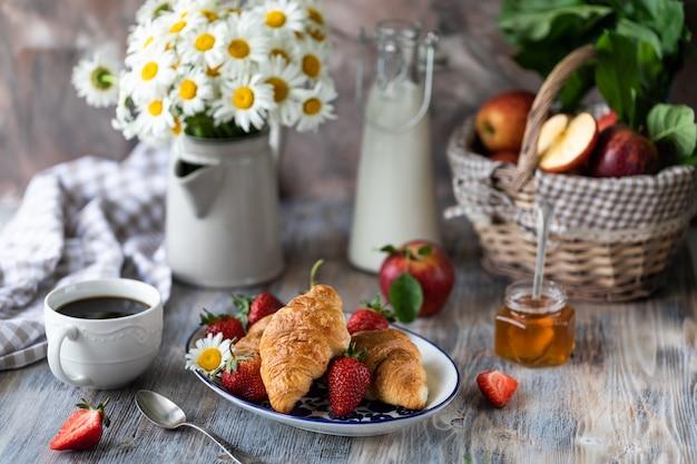 Hörnchen mit frischen roten erdbeeren mit einem tasse kaffee auf einem holztisch und einem blumenstrauß von gänseblümchen in einem krug.