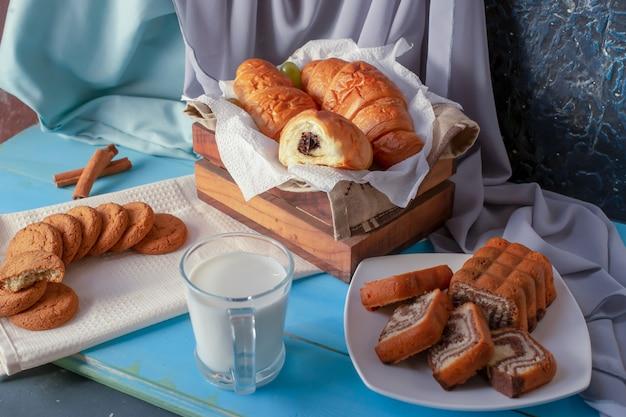 Hörnchen mit schokoladencreme, vanilletorte und plätzchen mit einer schale milch auf dem blauen holztisch.