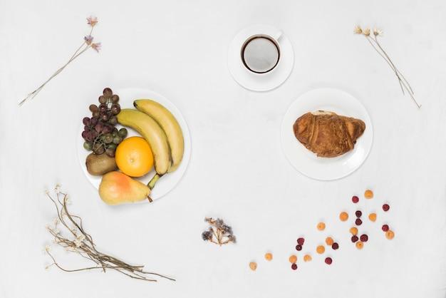Hörnchen und früchte auf weißer platte mit kaffee und trockenblumen auf weißem hintergrund
