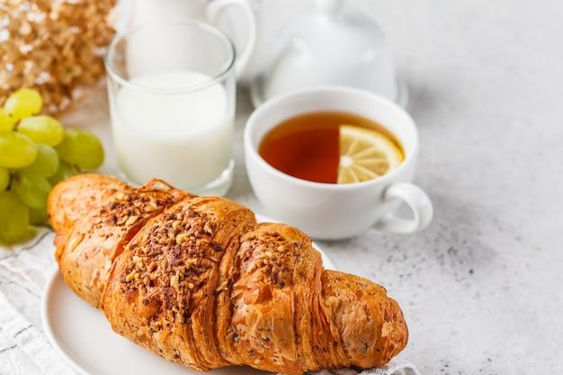 Hörnchen und tee zum frühstück auf weißem hintergrund, kopienraum.