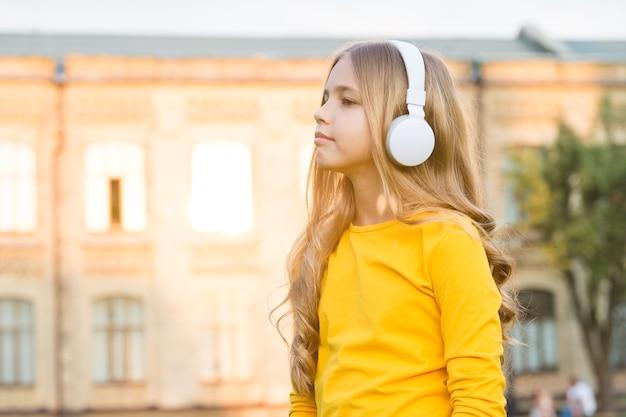 Hörst du genau zu. kleines kind hört musik im freien. kleine zuhörer tragen kopfhörer. aktivitäten zum zuhören. entspannen und zuhören. modernes leben. fühle die musik, die du hörst.