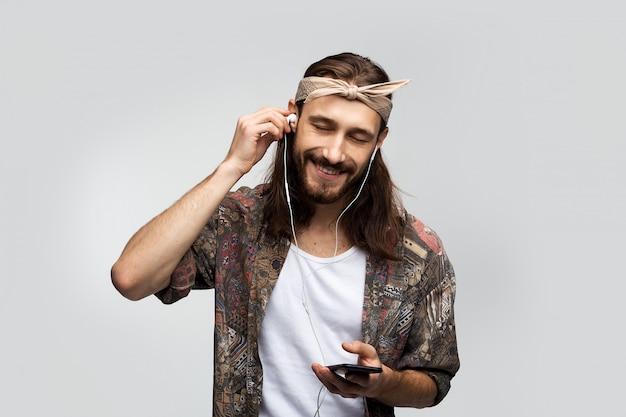 Hört musik und entspannt sich, genießt, gut aussehender langhaariger hippie-mann in kopfhörern mit einem smartphone in den händen auf weißem hintergrund