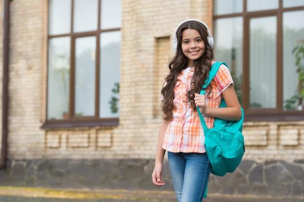 Hörübungen auf reisen. glückliches kind trägt rucksack im freien. wortschatz reisen. englische schule. sommererziehung. reisen und reisen. entdeckung und fernweh. modernes leben. neue technologie.