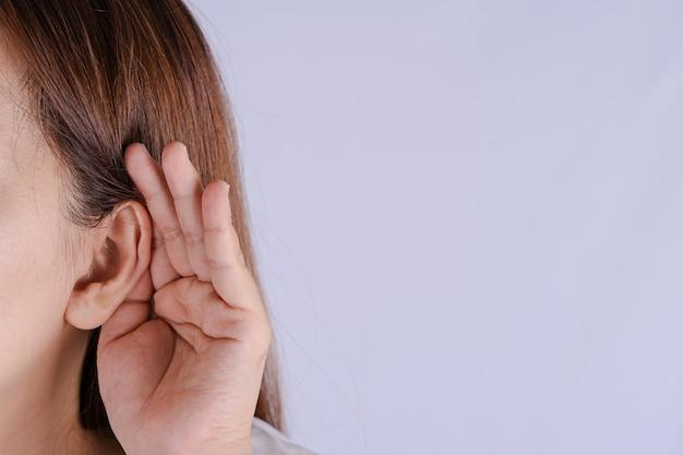 Hörverlust oder schwerhörigkeit der frau und ihre hand hinter ihrem ohr isolieren grauen hintergrund, taubes konzept.