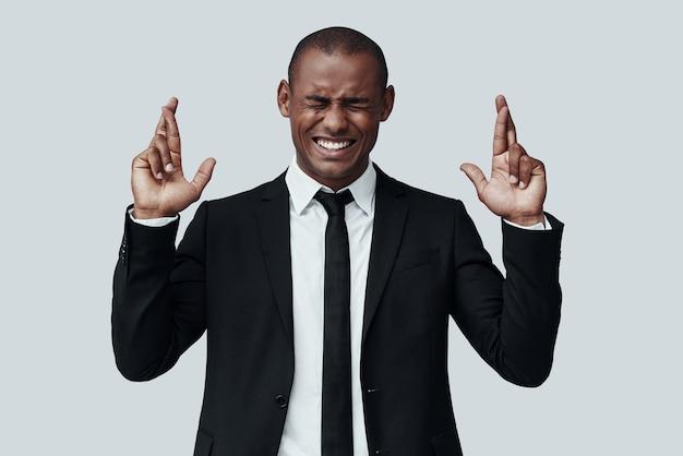 Hoffen für das beste. hübscher junger afrikanischer mann in formeller kleidung, der die augen geschlossen hält und die daumen drückt, während er vor grauem hintergrund steht
