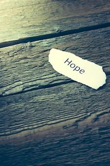 Hoffnung auf papier auf holztisch geschrieben