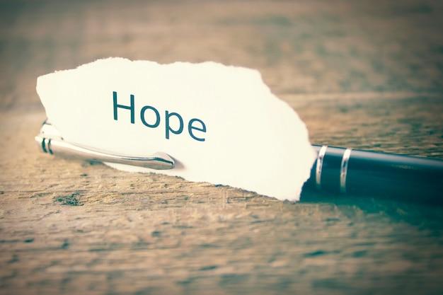 Hoffnung auf papier und stift auf holztisch geschrieben