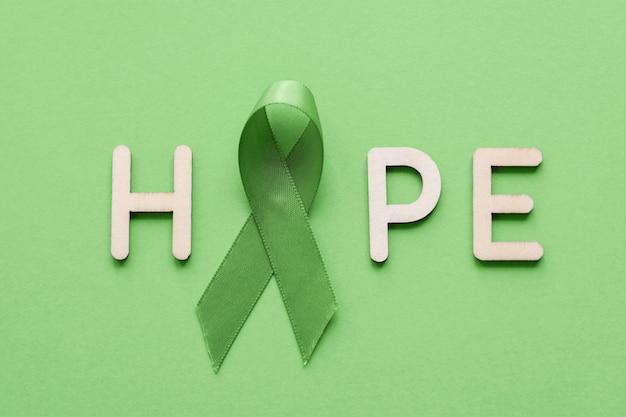 Hoffnung gemacht vom hölzernen buchstaben mit lindgrün-band auf grünem hintergrund