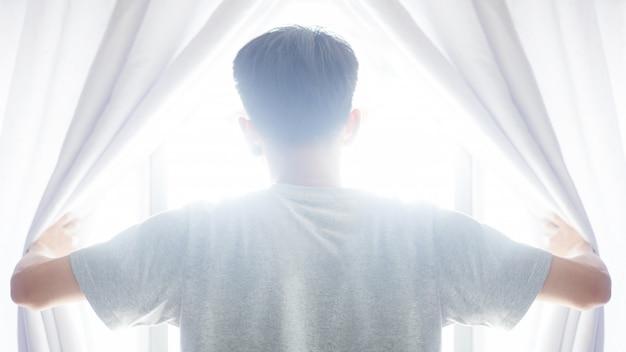 Hoffnung konzept. offener vorhang des mannes sehen sonnenaufgang