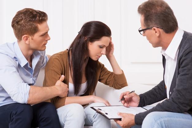 Hoffnungslos fühlen. junger mann tröstet seine depressive frau, während er mit einem psychiater zusammensitzt