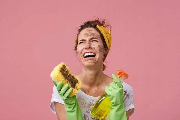 Hoffnungslose weinende hausfrau mit schmutziger kleidung und gesicht, die freizeitkleidung und handschuhe trägt und schwamm und waschmittel in händen hält, die krank und müde vom aufräumen sind. junges mädchen, das viel arbeit zu tun hat