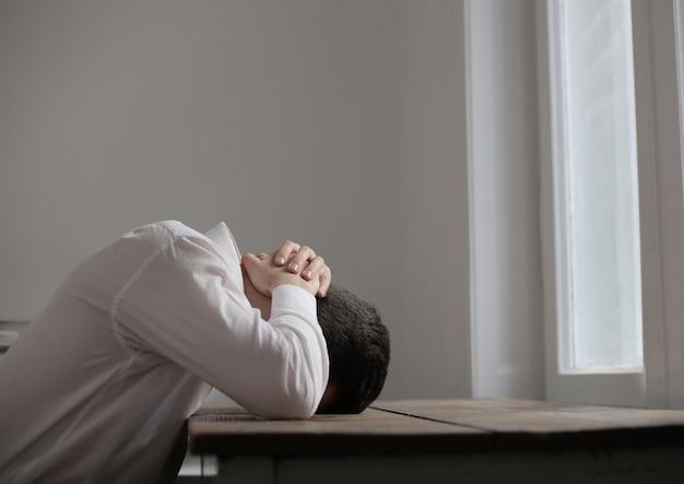 Hoffnungsloser unglücklicher trauriger mann an einem schreibtisch